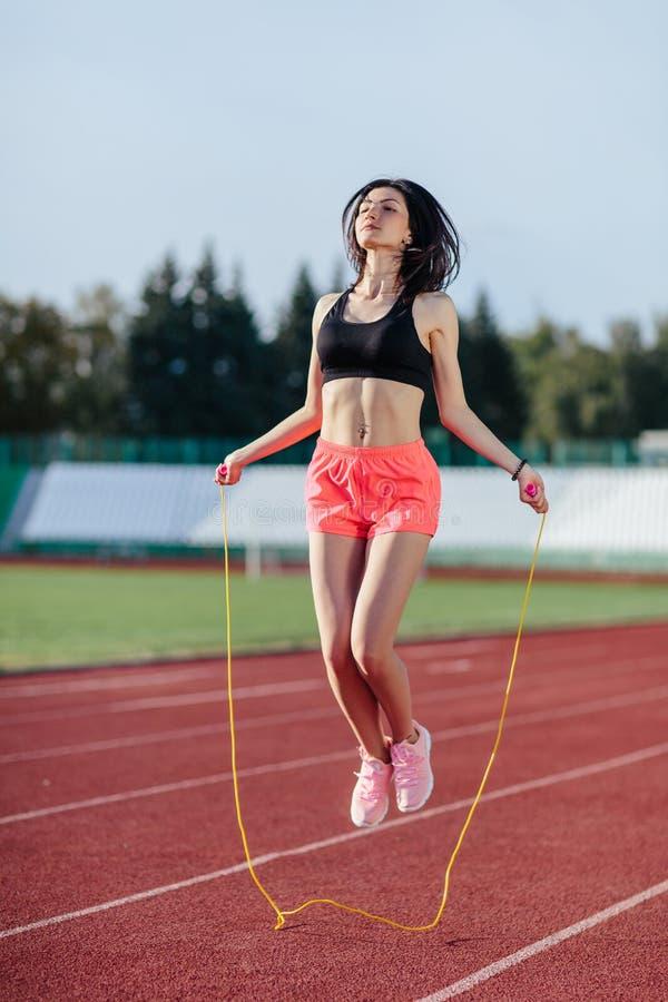 Conseguindo os melhores resultados Mulher moreno nova bonita na corda de salto da roupa dos esportes e sorriso ao exercitar no fotografia de stock