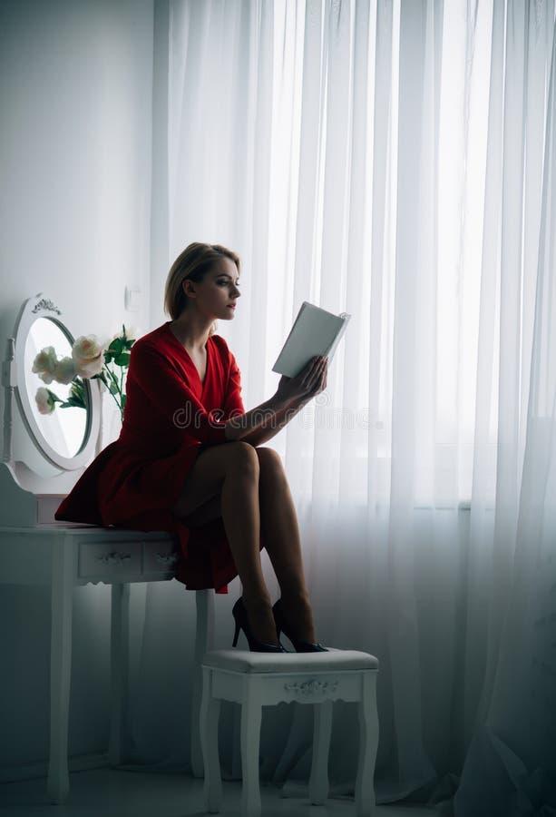 Conseguir la información mujer que consigue la información del libro interesante conseguir la información de la mujer en sitio de foto de archivo