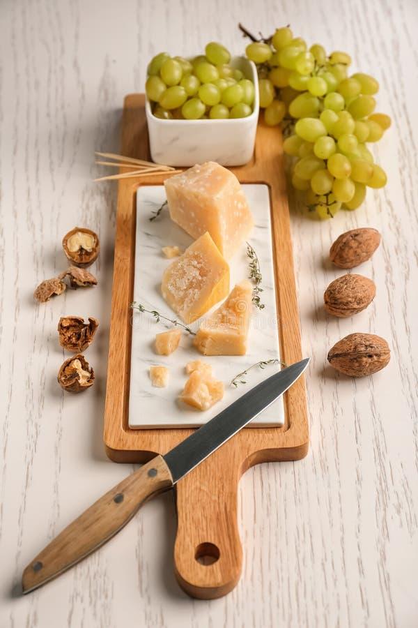 Conseil avec du fromage et les raisins savoureux sur la table en bois blanche photos libres de droits