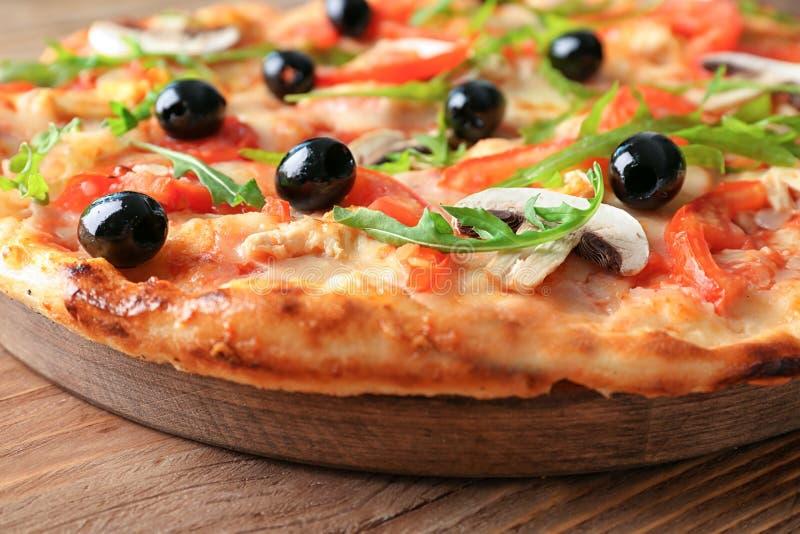 Conseil avec la pizza italienne savoureuse sur la table en bois, plan rapproché image stock