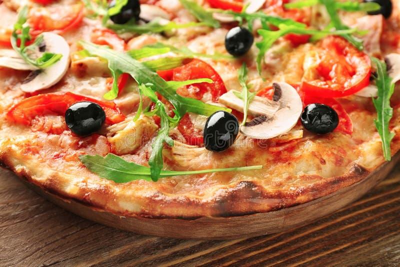 Conseil avec la pizza italienne savoureuse sur la table en bois, plan rapproché photographie stock libre de droits