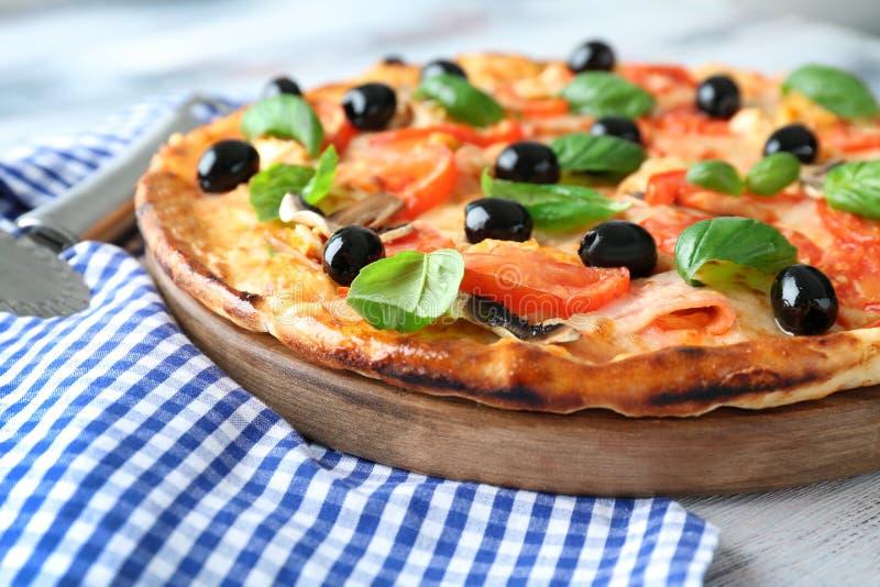 Conseil avec la pizza italienne savoureuse sur la table en bois, plan rapproché photos stock