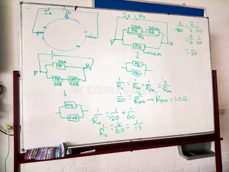 Conseil blanc avec le dessin schématique et les formules d'un circuit électrique Classe de physique photographie stock libre de droits
