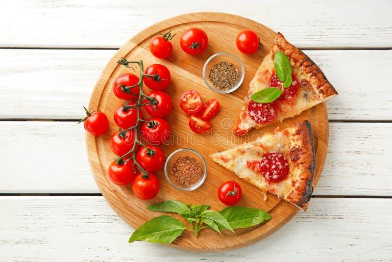 Conseil en bois avec des tranches de pizza et d'épices délicieuses sur la table photos libres de droits