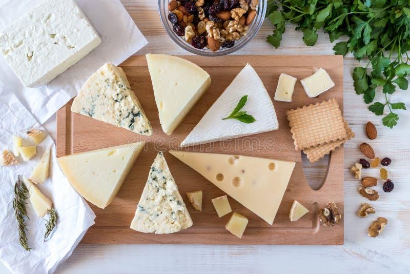 Conseil en bois avec différents genres de fromage délicieux avec des écrous photos libres de droits