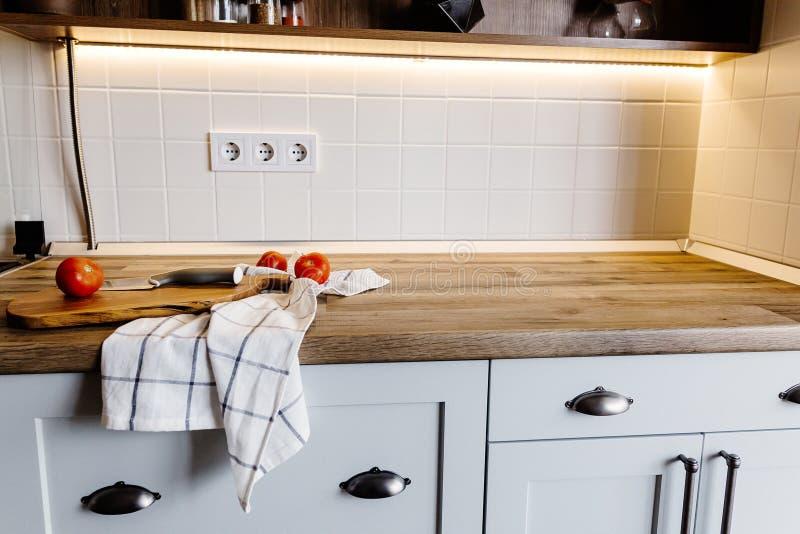 Conseil en bois avec le couteau, tomates, serviette sur le compte moderne de cuisine images libres de droits