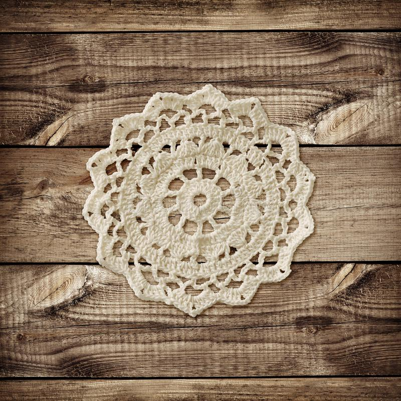 Conseil en bois de Brown et petit napperon de crochet photographie stock libre de droits