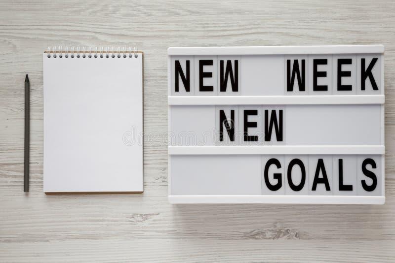 """Conseil moderne avec buts nouvelle semaine des textes de """"de nouveaux """", crayon et bloc-notes au-dessus du fond en bois blanc, vu photographie stock"""