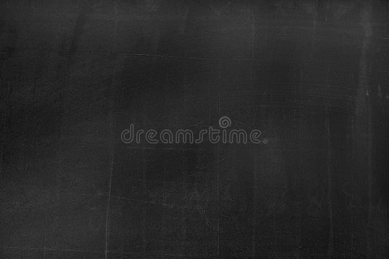 Conseil noir avec les traces de la craie au-dessus de sa surface comme fond photos stock
