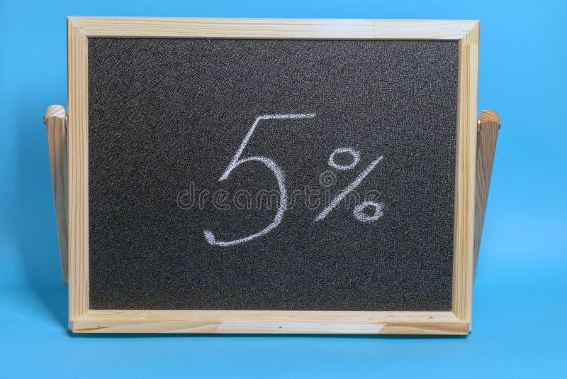 Conseil noir dans un cadre en bois sur un fond bleu avec l'inscription 5 pour cent Maquette pour faire des emplettes, ventes photographie stock libre de droits