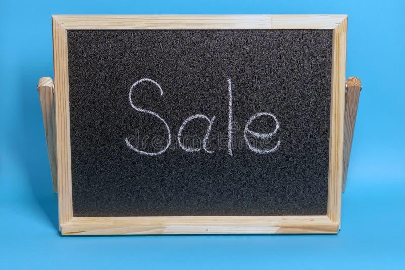 Conseil noir dans un cadre en bois sur un fond bleu avec la vente d'inscription Maquette pour faire des emplettes, ventes, vendre photographie stock libre de droits