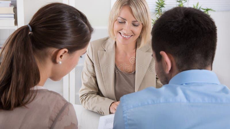 Conseiller, courtier et clients s'asseyant au bureau dans le bureau image stock