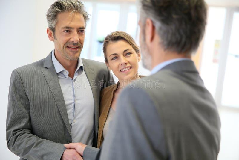 Conseiller d'opérations bancaires et poignée de main de clients image stock
