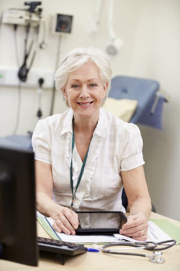 Conseiller féminin Working At Desk à l'aide de la Tablette de Digital photo stock