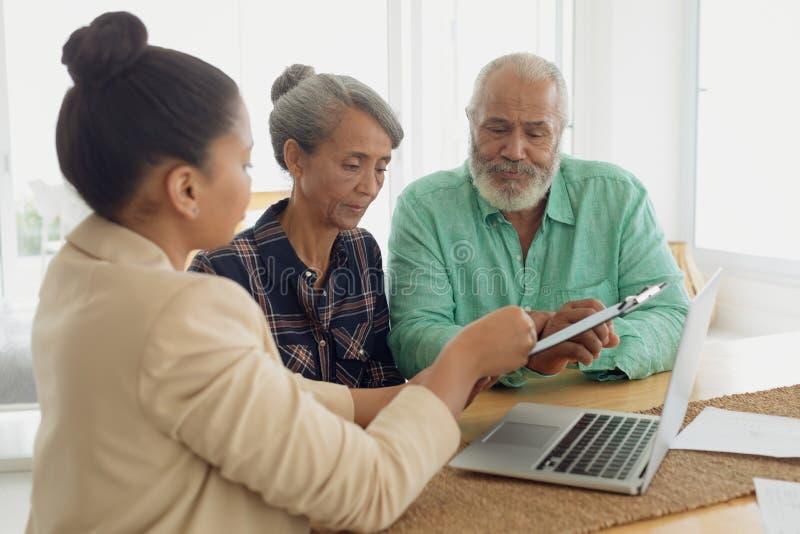Conseiller financier discutant l'information avec un couple images libres de droits