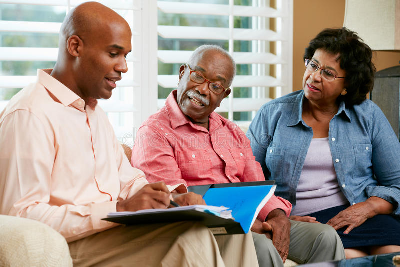 Conseiller financier parlant aux couples supérieurs à la maison photos stock
