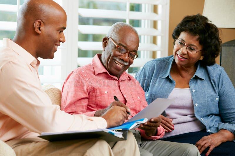 Conseiller financier parlant aux couples supérieurs à la maison photos libres de droits