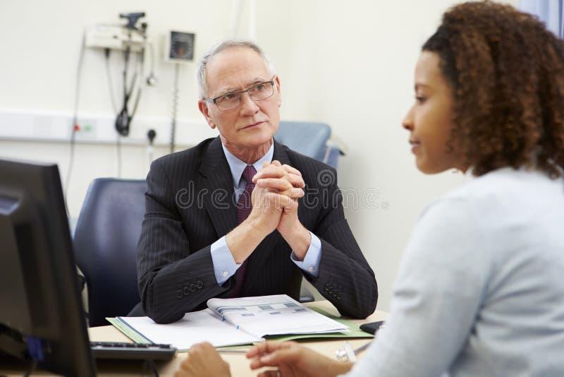 Conseiller Meeting With Patient dans le bureau images libres de droits