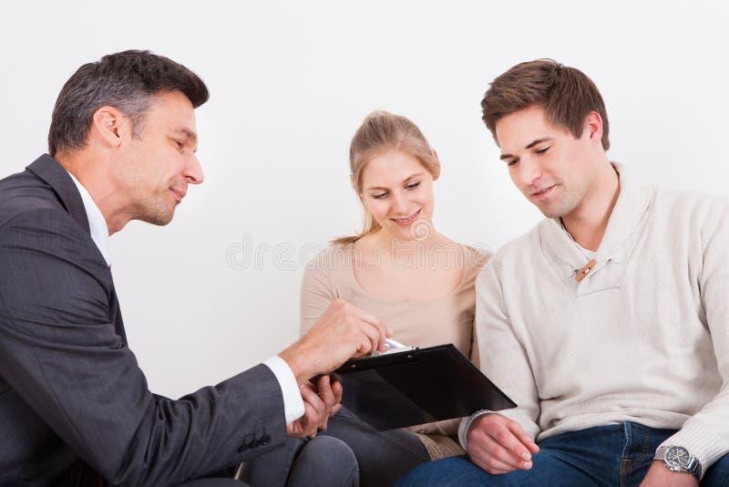 Conseiller montrant le presse-papiers aux couples photo libre de droits
