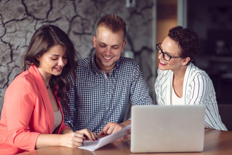Consejero de inversi?n que da una presentaci?n a un par joven sonriente amistoso asentado en su escritorio en la oficina imagen de archivo libre de regalías