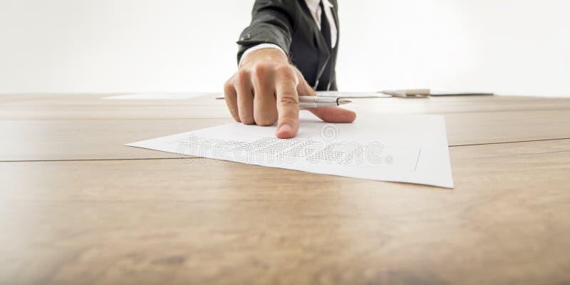 Consejero de negocio que muestra a un pedazo de documento con estadístico foto de archivo libre de regalías
