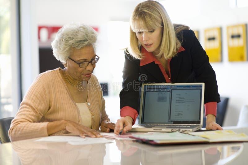 Consejero financiero que ayuda a la mujer mayor fotografía de archivo