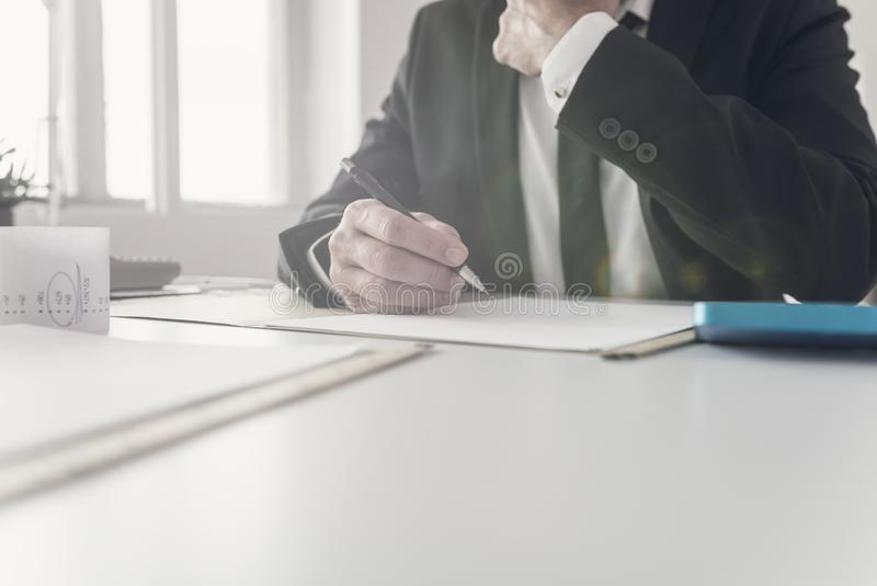 Consejero financiero que trabaja en su escritorio fotos de archivo