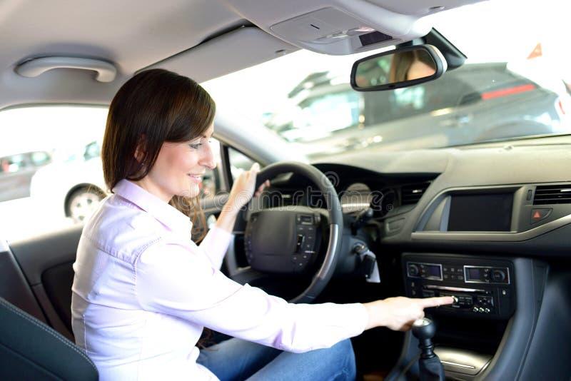 Consejo de la concesión de coche - sentada y prueba de la mujer joven en un nuevo fotografía de archivo