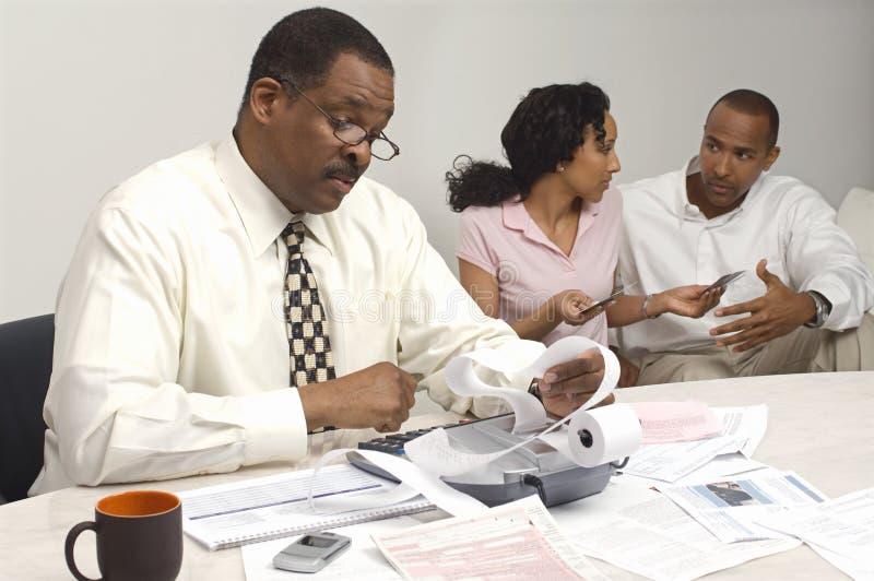 Conselheiro financeiro que guarda o recibo da despesa com pares no fundo foto de stock