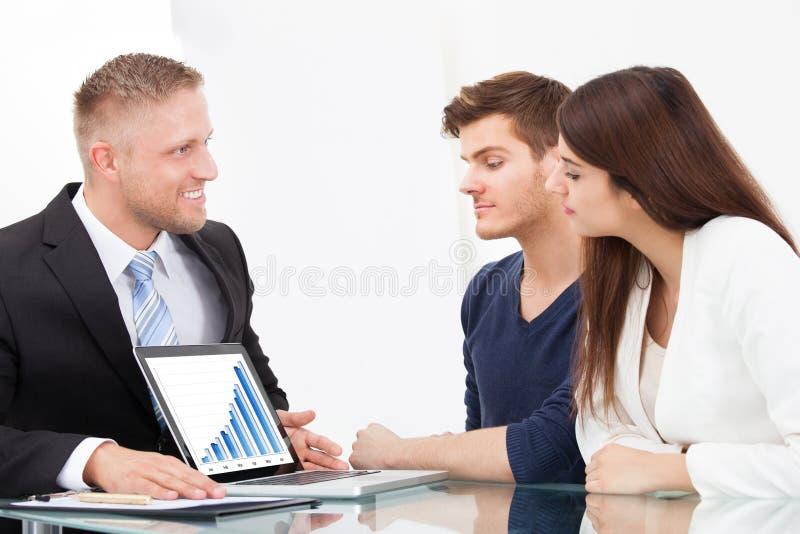 Conselheiro que mostra planos de investimento aos pares no portátil imagens de stock