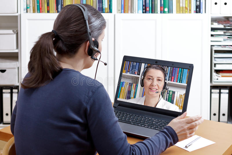 Conselheiro video da consulta dos auriculares das mulheres fotografia de stock