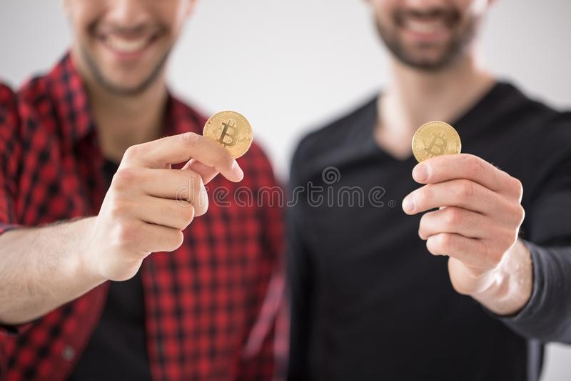 Conselheiros financeiros de sorriso com símbolo do cryptocurrency virtual fotos de stock royalty free