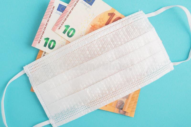 Consequências da epidemia de coronavírus Conceito de crise financeira Notas de euro e máscara anti-bacteriana médica em azul imagens de stock