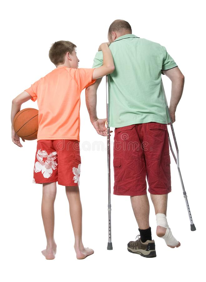 The Consequences of Injury. A men unable to play a game with his son due to a work related injury, safety concept stock photos