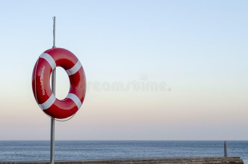 Conservante de vida no Sandy Beach de Cascais em Portugal no por do sol foto de stock