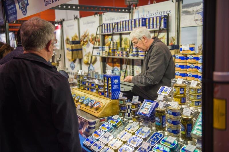 Conservas de compra dos peixes dos povos no mercado fotografia de stock royalty free