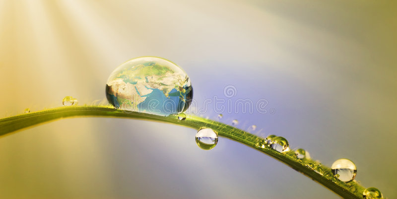 Conservation concept:earth in a droplet. Conservation concept: macroshot of droplets with earth reflection stock image