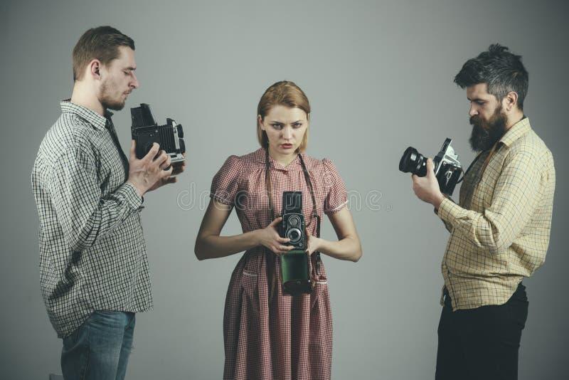 Conservation de vos meilleurs souvenirs Studio de photographie La rétro femme et les hommes de style tiennent les caméras analogu photographie stock