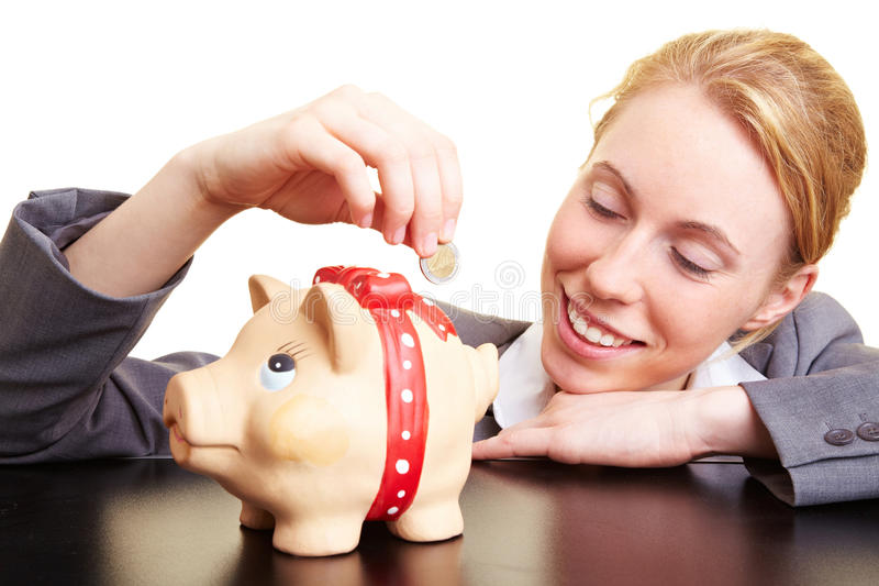 Conservative investment. Businesswoman dropping a coin in a piggy bank royalty free stock photo