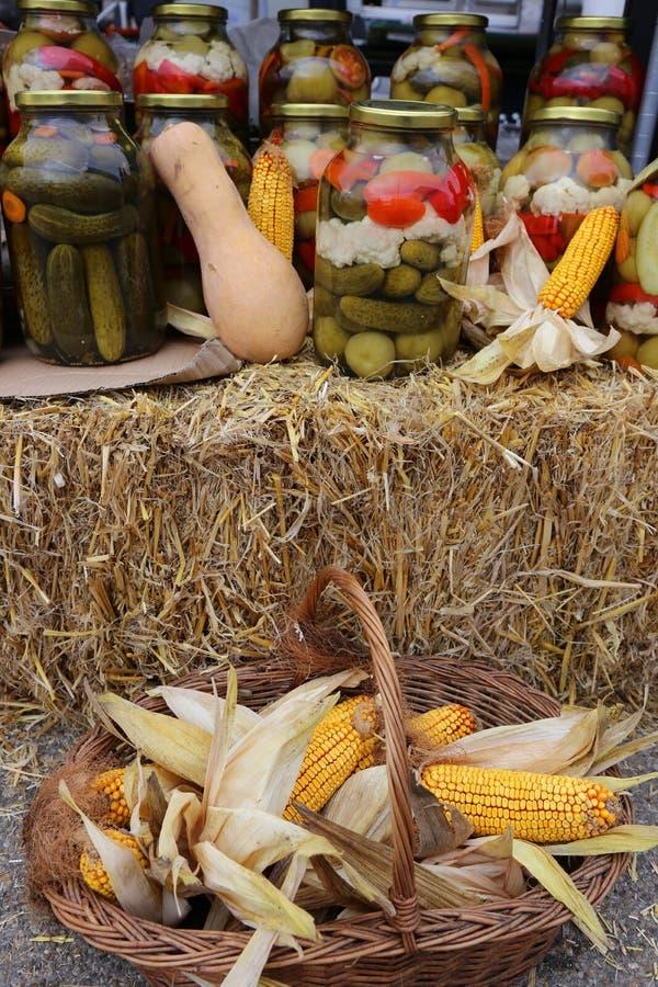 Conserves au vinaigre d'automne et un panier des épis de maïs image stock