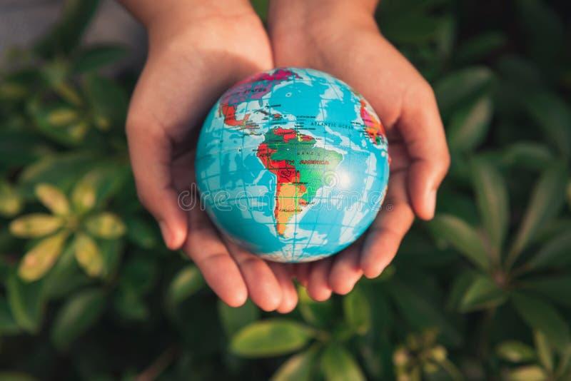 Conservi il concetto della terra, donna che le mani sta tenendo il modello il globale immagine stock