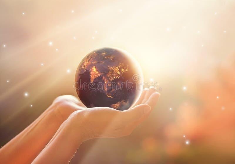 Conservi la campagna dell'energia mondiale Pianeta Terra sulla manifestazione umana delle mani fotografia stock libera da diritti