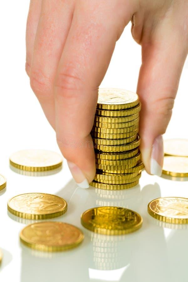 Conservi la donna con la pila di monete su soldi fotografia stock