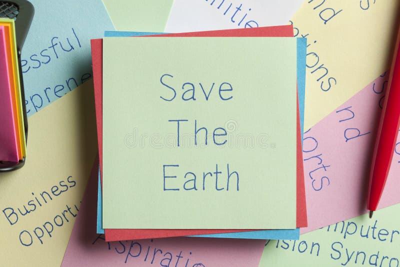 Conservi la terra scritta su una nota immagini stock