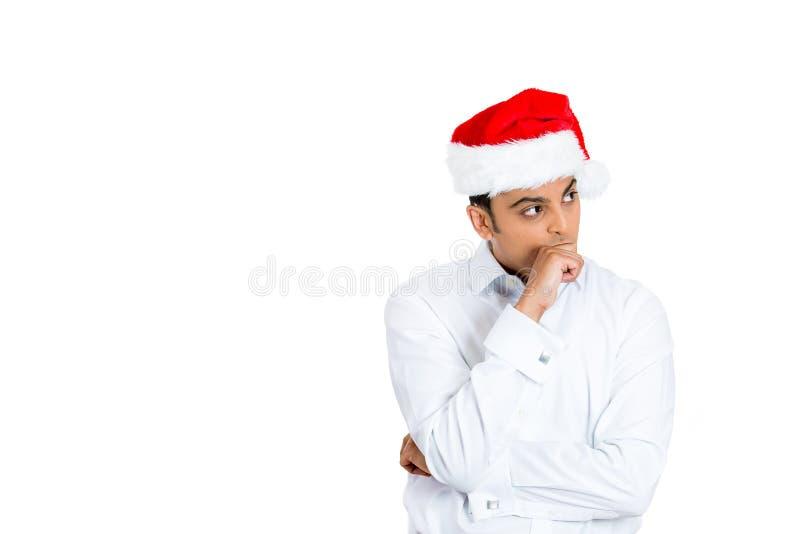 Considérer et jeune homme méfiant dans le chapeau rouge de Santa photographie stock