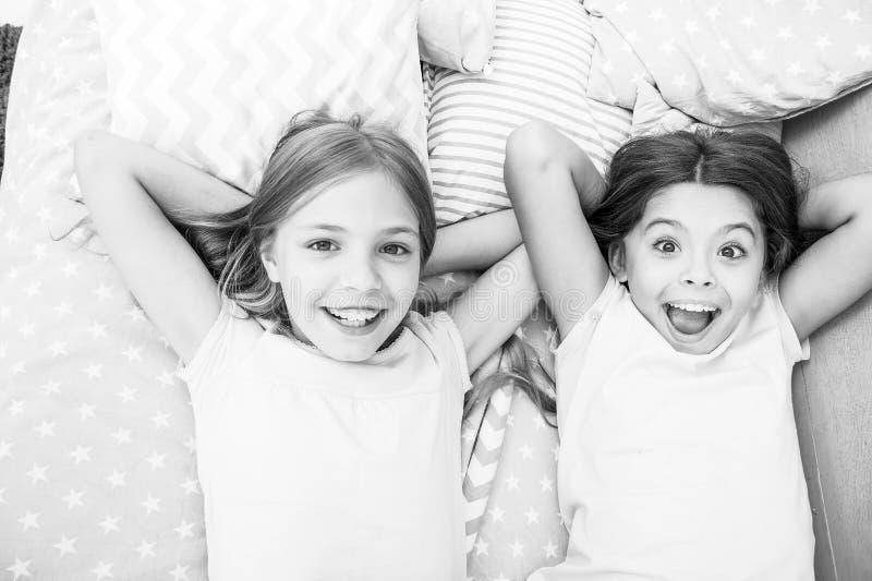Considérez la soirée pyjamas de thème Tradition intemporelle d'enfance de soirée pyjamas Filles détendant sur le lit Concept de s image libre de droits