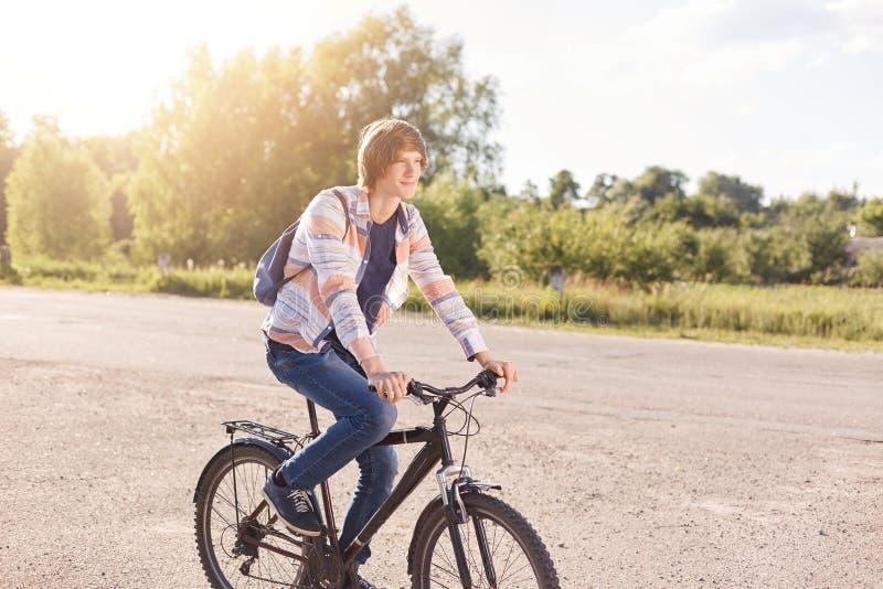 Considerável com a camisa vestindo e as calças de brim do penteado na moda que têm a trouxa na bicicleta traseira da equitação na imagem de stock royalty free