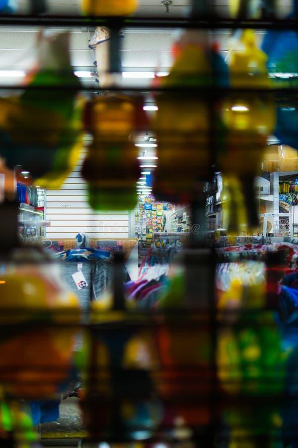 Considerando a través de una exhibición de la ventana y de una puerta cerrada del descenso, en una tienda al por menor la noche,  imágenes de archivo libres de regalías