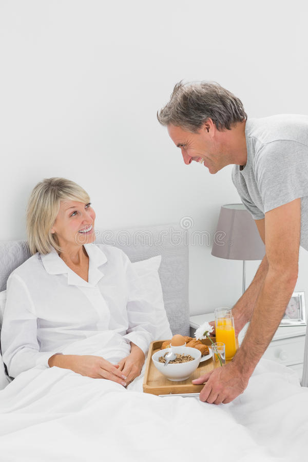 Considerate Man Bringing Breakfast In Bed To His Partner Stock Photography