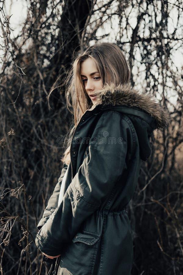 Consideravelmente e jovem mulher da forma no Parka que está no perfil à câmera fotos de stock royalty free